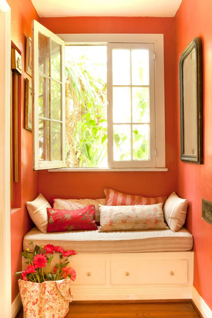 Every corner of the home is put to use, such as this cozy nook that boasts comfortable seating and a lovely view through French-style windows.