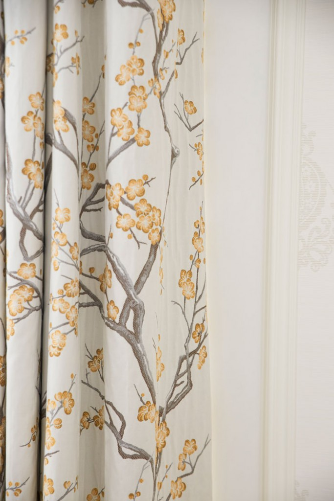 Light and fresh, the faux bois patterned draperies in this room create a clean and crisp experience.