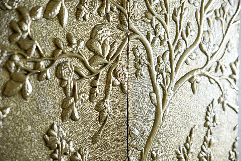 An intricately designed, gold wall art acts as the focal decor piece in the hallway leading to the main bedroom.