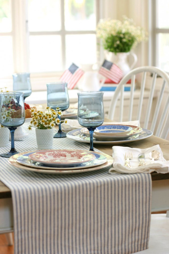 Vibrant blue glassware compliments the ticking stripe table runner, while sweet little chamomile flowers in white hobnail votive holders add a cheerful splash of color.