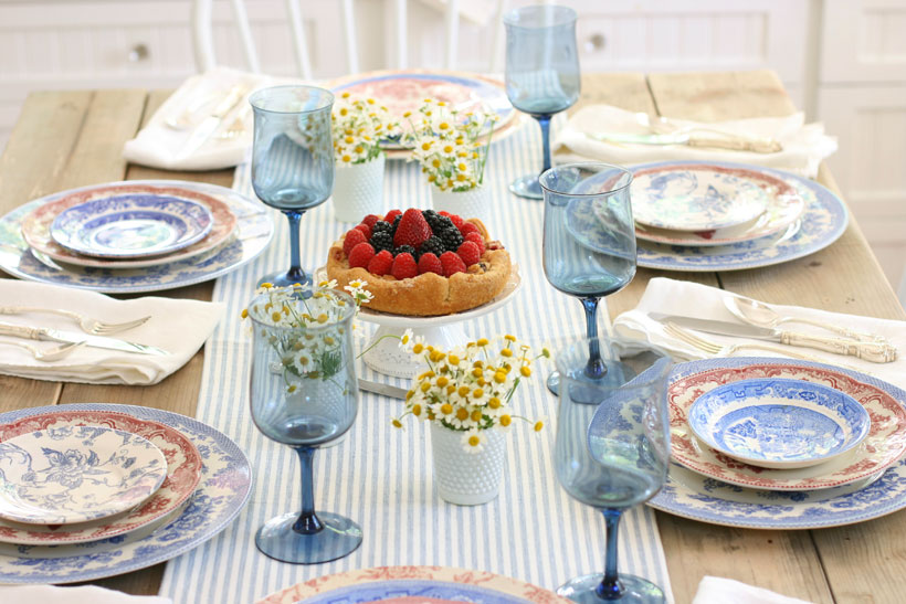 A pretty berry tart sits upon a pedestal at the center of the table and sets the tone for the patriotic colors of this tablescape and offers a preview to the delicious meal awaiting guests.