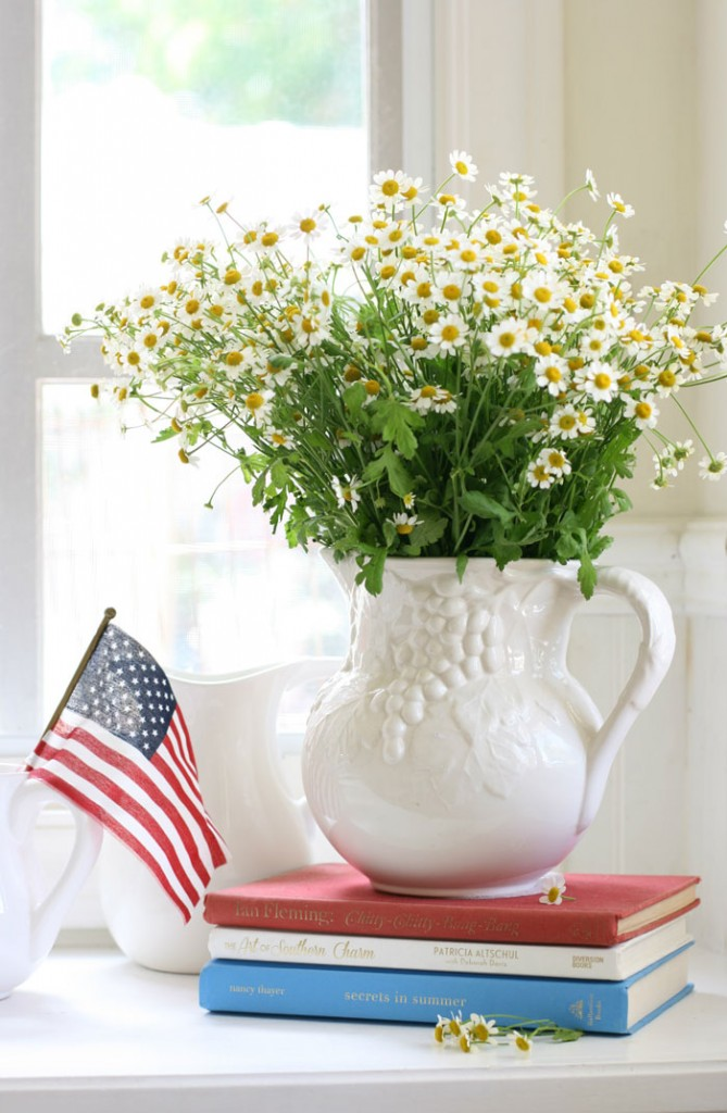 A lovely pitcher of chamomile flowers is elevated with a playful accent of red, white and blue books.