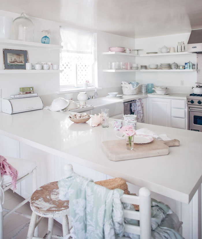 The kitchen is a white canvas, with glossy and matte finishes adding dimension and pops of pink and blue to accent the space in the Shabby Chic beach house.