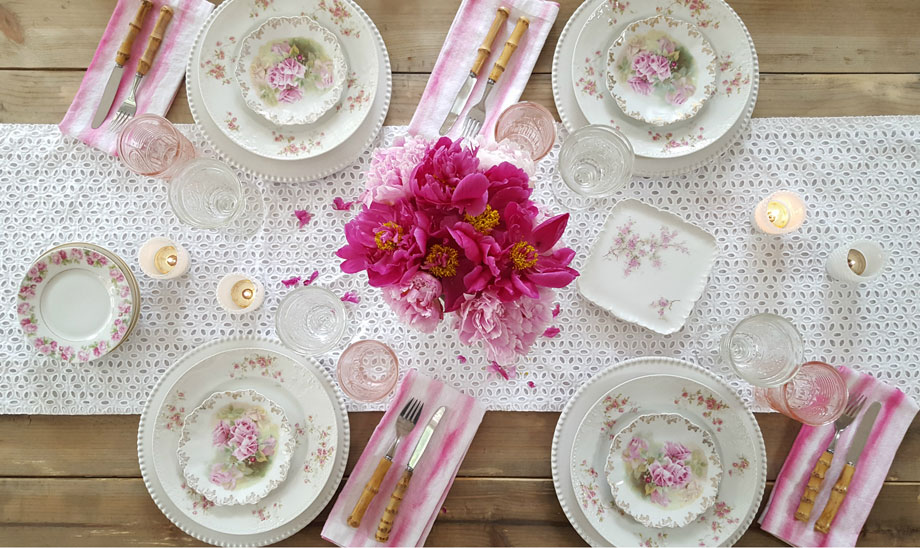 A bird's eye view of this table shows how to collect and display rose patterned china. Modern elements like ombre napkins, fresh flowers, and a stylish eyelet tablerunner keep it from looking too old-fashioned.