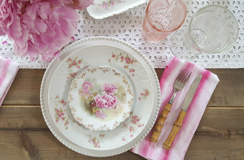 Small and large patterns of roses on each plate complement each other, while the vibrant pink hues in the flowers and napkins punctuate the vibrancy of the pink roses at the center of each place setting.