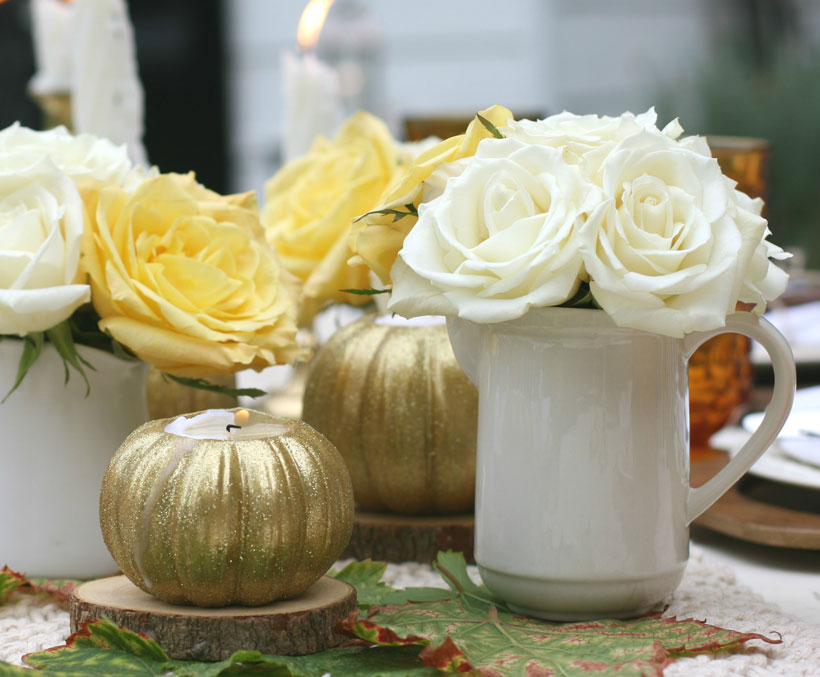 A trio of ironstone creamers holds white and yellow roses alongside glittery pumpkins at this Thanksgiving table setting