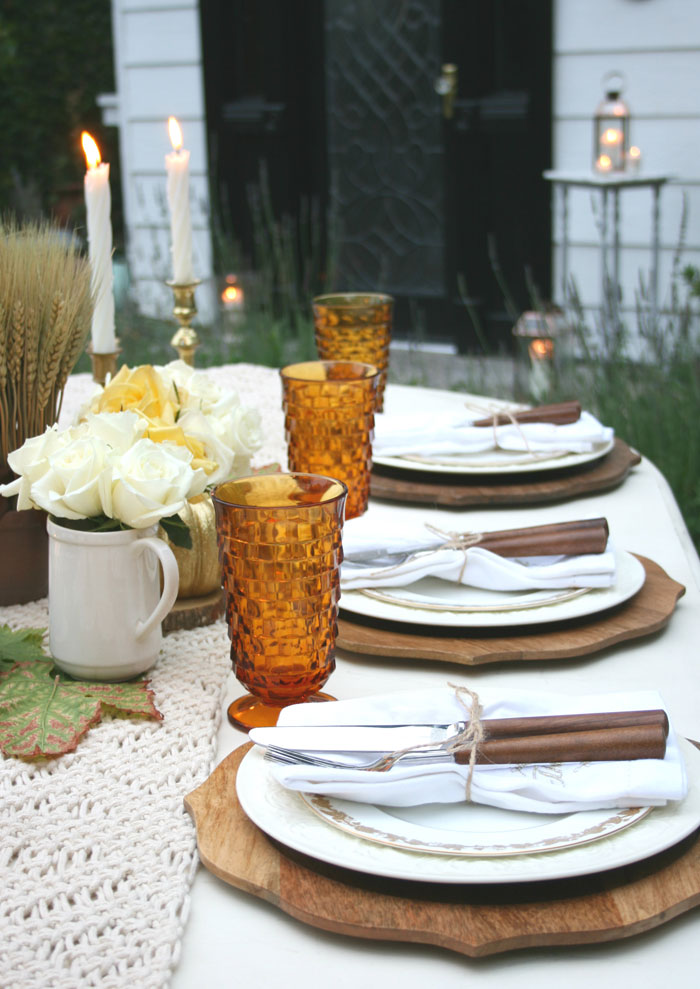 Cozy candlelight sets the ambiance of alfresco dining at this Thanksgiving table setting