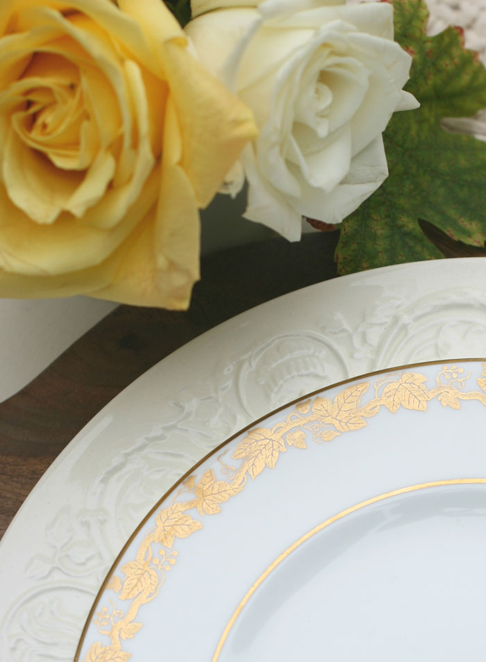 Accents of gold on the salad plate used in this Thanksgiving table setting coordinate beautifully with the brass candlesticks and yellow roses