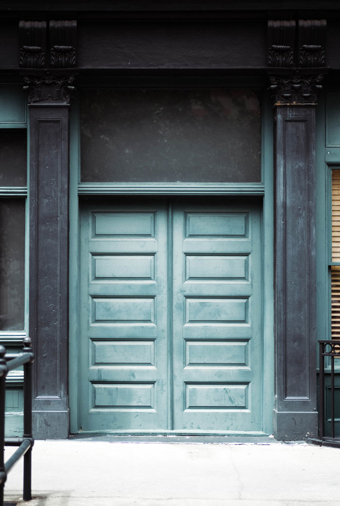 Architectural Details- Light aqua painted doors are surrounded by deep navy ornate columns and black wrought iron. Photo by Kayla Devito