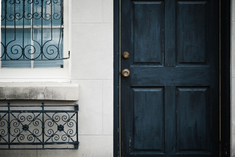 Architectural Details-A brushed navy blue door with mismatched wrought iron filigree details. Photo by Kayla DeVito.
