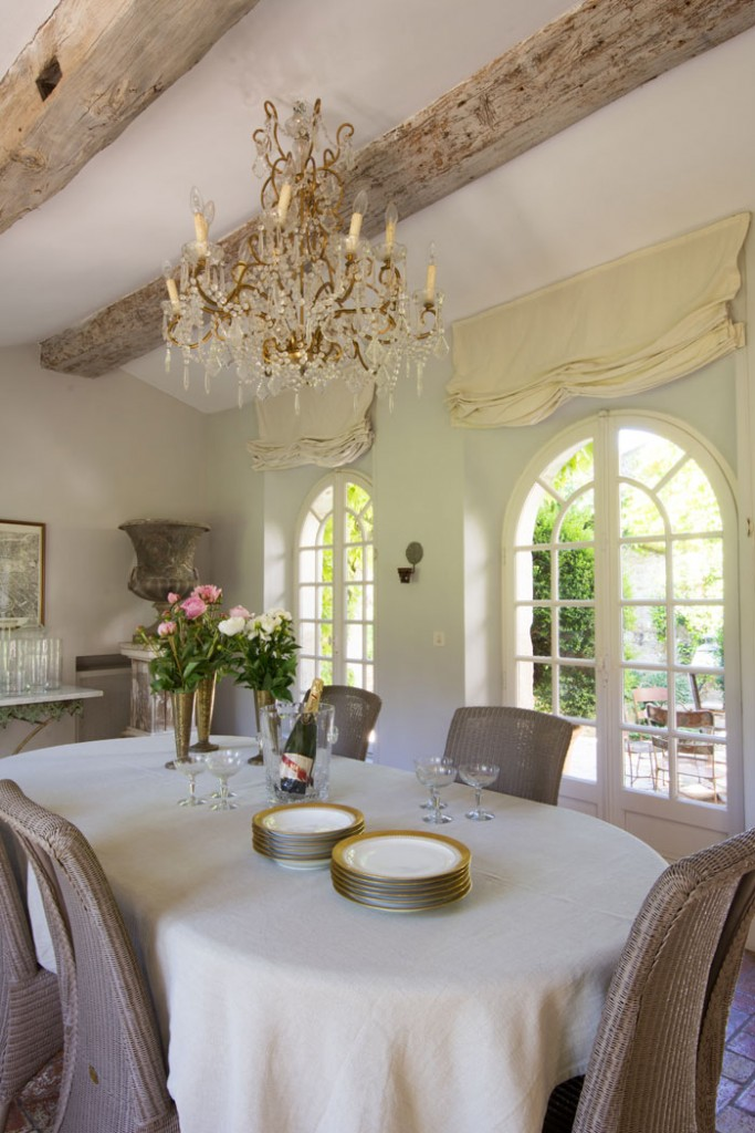 A testament to the 17th-century home, the dining room boasts original wood beams on the ceiling and red terra cotta tiles that were typical for that time period. A gilded-frame antique chandelier brings elegance to the space, while garden chairs surrounding the table give the room a relaxed vibe.