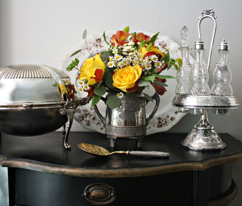 """Silver is considered a """"cool tone."""" Lidy added warmth to her sideboard vignette by adding bright yellow and red blossoms."""