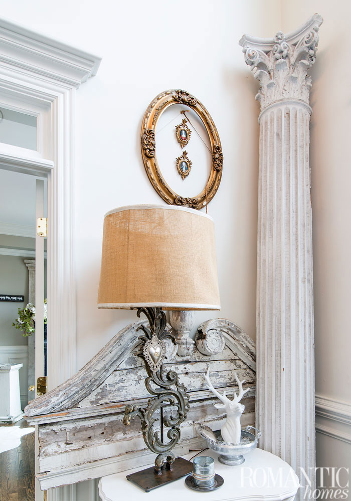 A Corinthian column leans in the corner while an old French frame encircles mini cameos, adding to the room's vintage decor