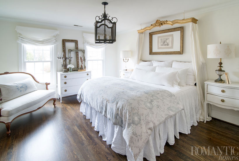 The vintage decor of the bedroom features a French cornice hanging from the ceiling as a sort of canopy for the bed.