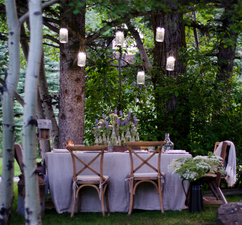 The solar-powered jar lights hung high in the tree branches seem to float over the dinner table. Complete with the soft fabrics and pale color palette, the woodland setting provides a magical quality to the evening's ambiance.