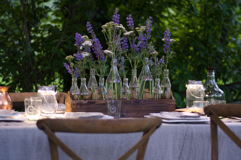 Clear bottles in a variety of sizes line the interior of a narrow wooden crate. The bottles hold a chorus of lupin and yarrow, utilizing the natural flowers from the surrounding area.