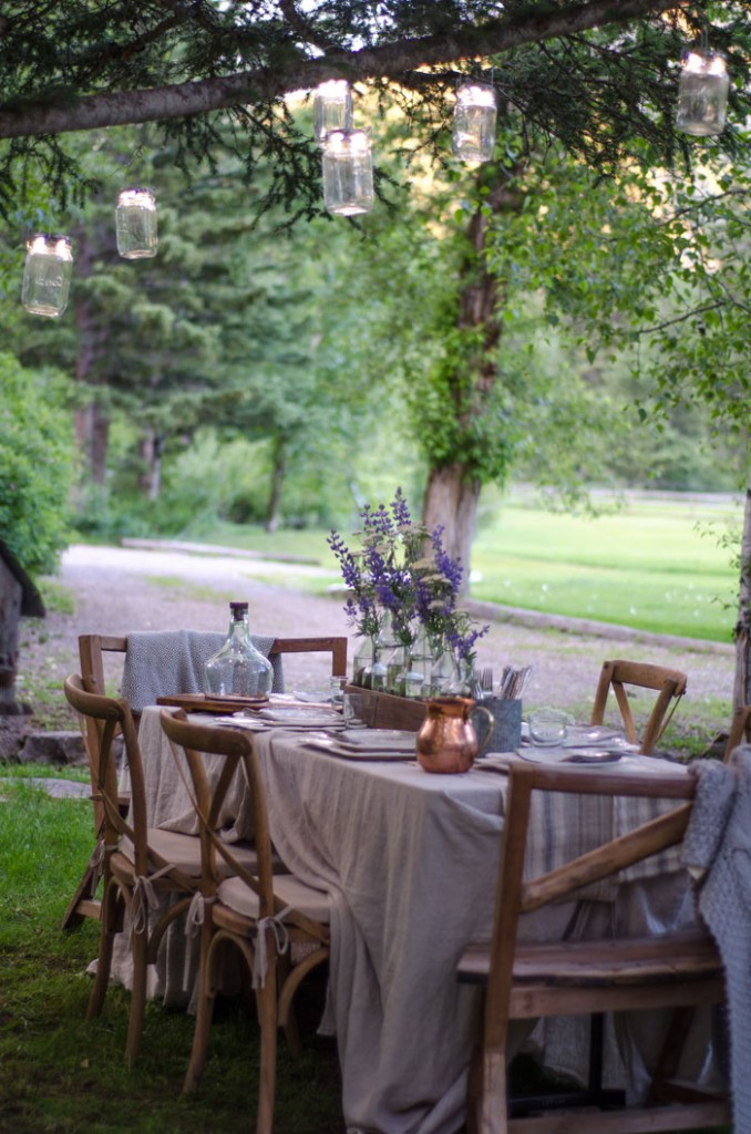 Hanging solar LED mason jar lights add ambiance and warmth the the outdoor table setting.