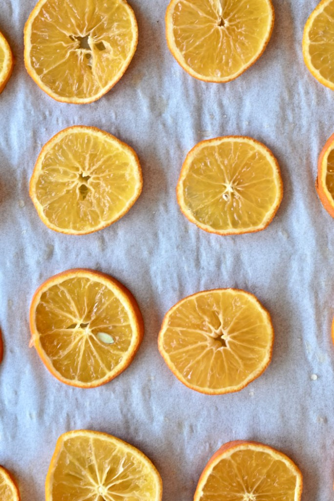 Line two baking sheets with parchment paper and lay out your citrus circles in rows.
