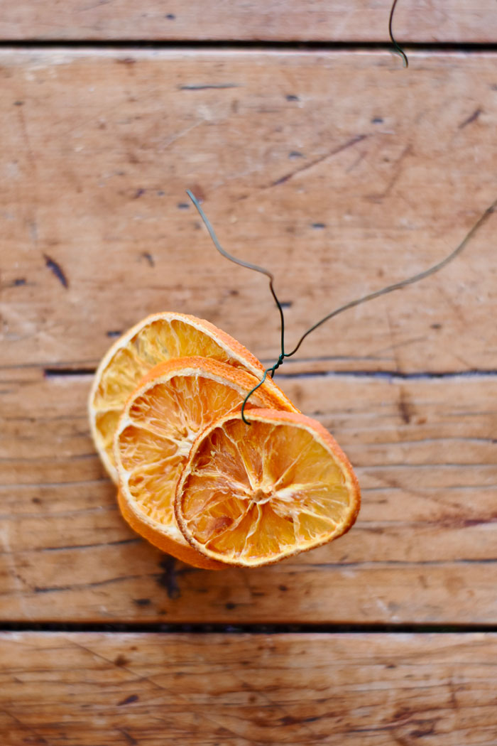Using the floral wire, create dried orange bundles (each with three slices).