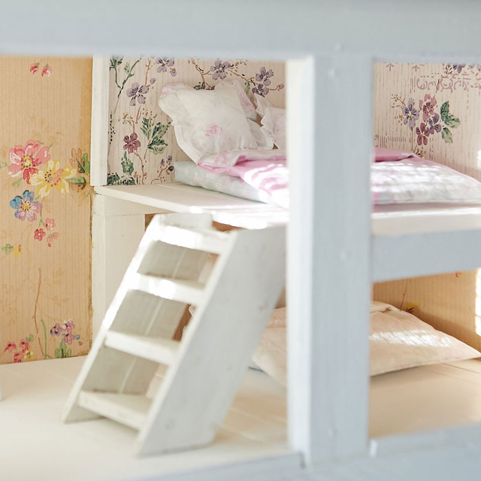 The bunkbed in this vintage dollhouse, complete with tiny ruffled pillows and a step ladder, is imaginative and whimsical. #romantichomes