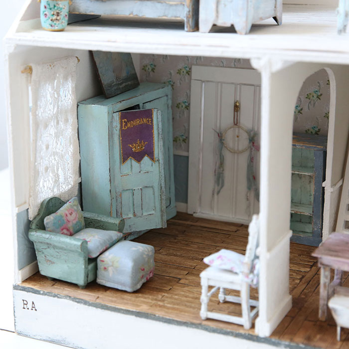 The details in this vintage dollhouse scene, hardwood floors, a poster hanging on the door of the armoire and a painting resting on top, simply can't be beat for their uniqueness and delicacy.