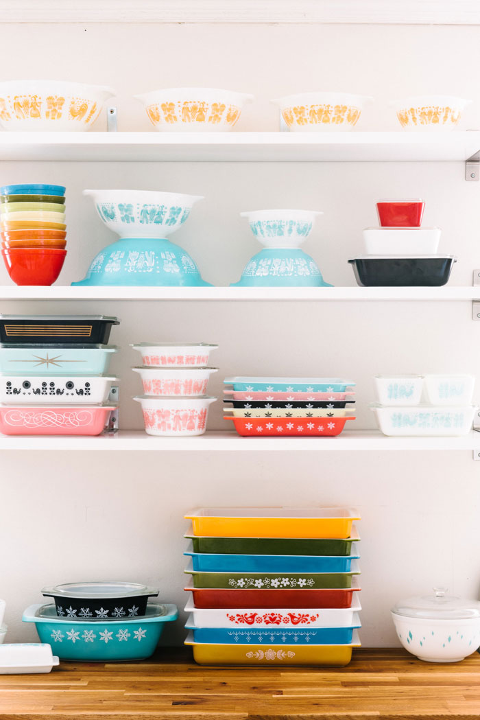 Both fun and practical, the open shelving kitchen trend is made for displaying collectibles like Pyrex. The Amish Butterprint features prominently in this display, with three colorways. Orange (top shelf), Turquoise (middle shelf, center), and Pink (bottom shelf, 2nd to left.)