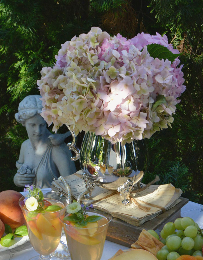 Stacked on an antique book and a bundle of hand-written letters for added height, this arrangement of fresh hydrangeas is perfectly suited for a simple and elegant event. #romantichomes