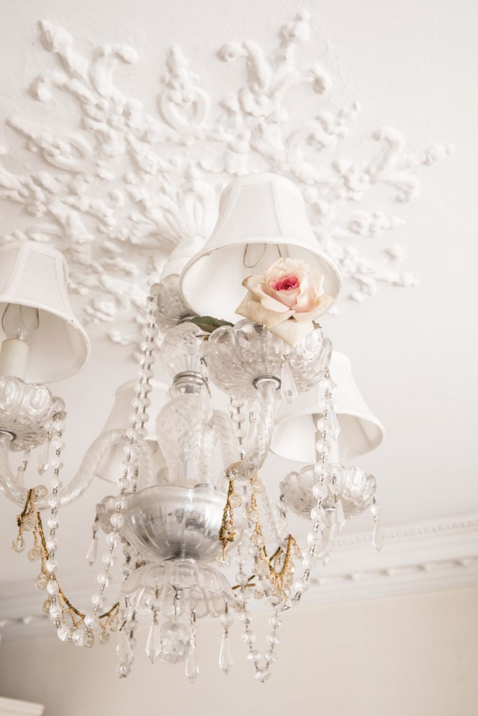 A rose tucked into the shade of a crystal chandelier.