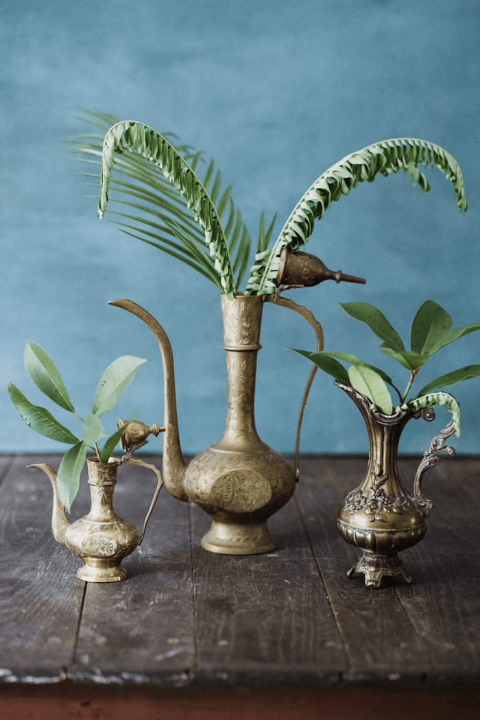 Three vintage brass vessels filled with fresh cut leaves