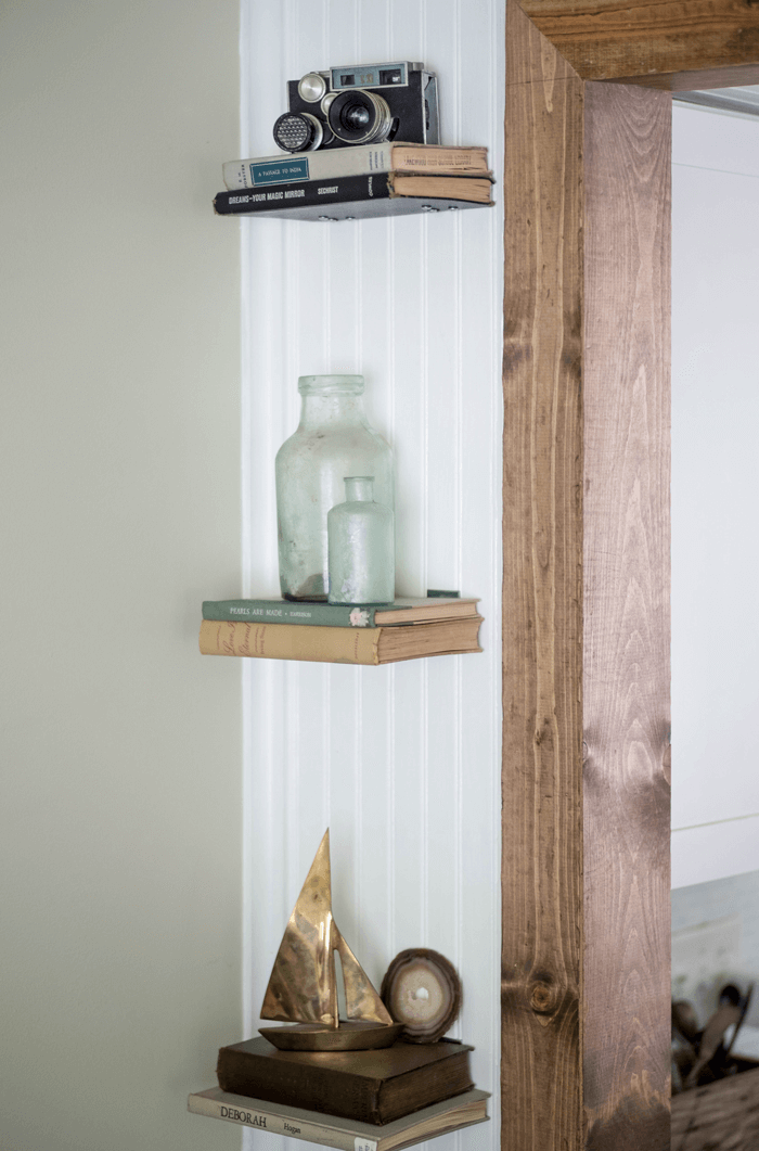 Book shelves with a brass boat, vintage camera and old glass jars
