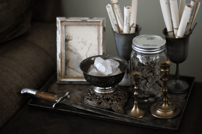 Table top vignette with crystals, music sheets, brass candlesticks, and WWI bayonet.