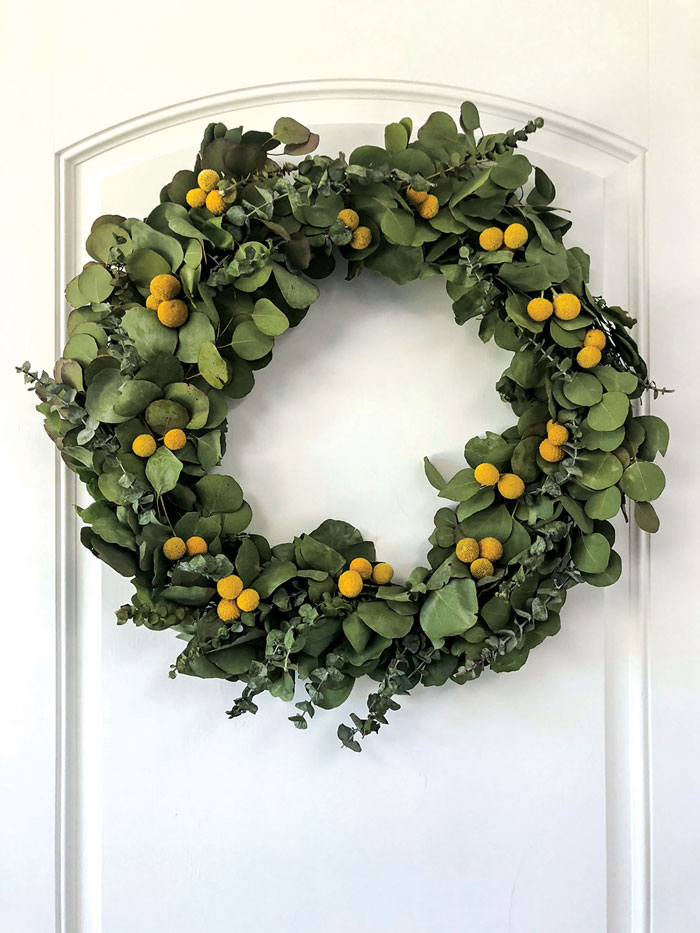 The key to arranging eucalyptus is in forming the greens around the frame while they are still supple and fresh. After letting the leaves dry for a few days, the dried craspedia balls were glued into position on the DIY wreath.