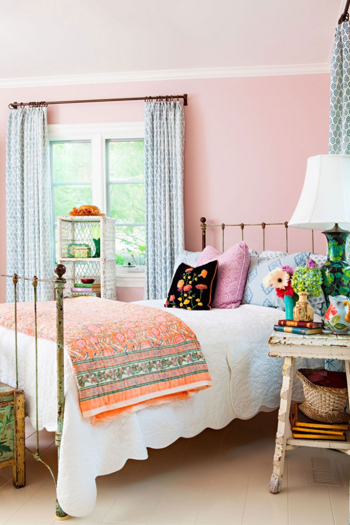 Wrought iron bed in a pink bedroom with a white quilt on the bed. How to Collect and Care for Quilts