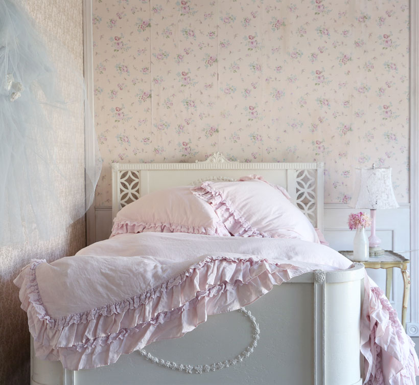 Rachel Ashwell's Shabby Chic bedroom with floral wallpaper, ruffled bedding and vintage furniture