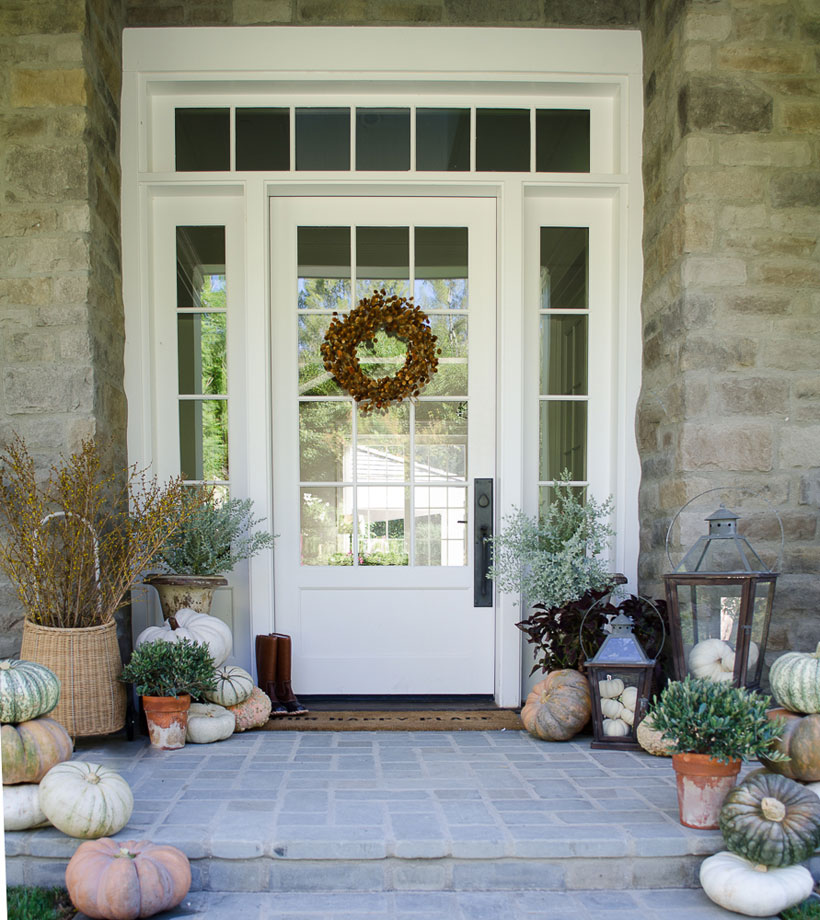 Karen Snyder's cozy front porch decorated for fall with heirloom pumpkins and oversized lanterns- Romantic Homes