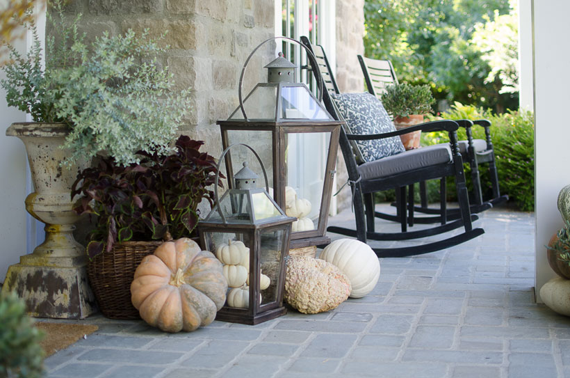 A deep burgundy Vino Coleus, heirloom pumpkins, oversized lanterns and a pair of rocking chairs create a cozy atmosphere on Karen Snyder's fall front porch