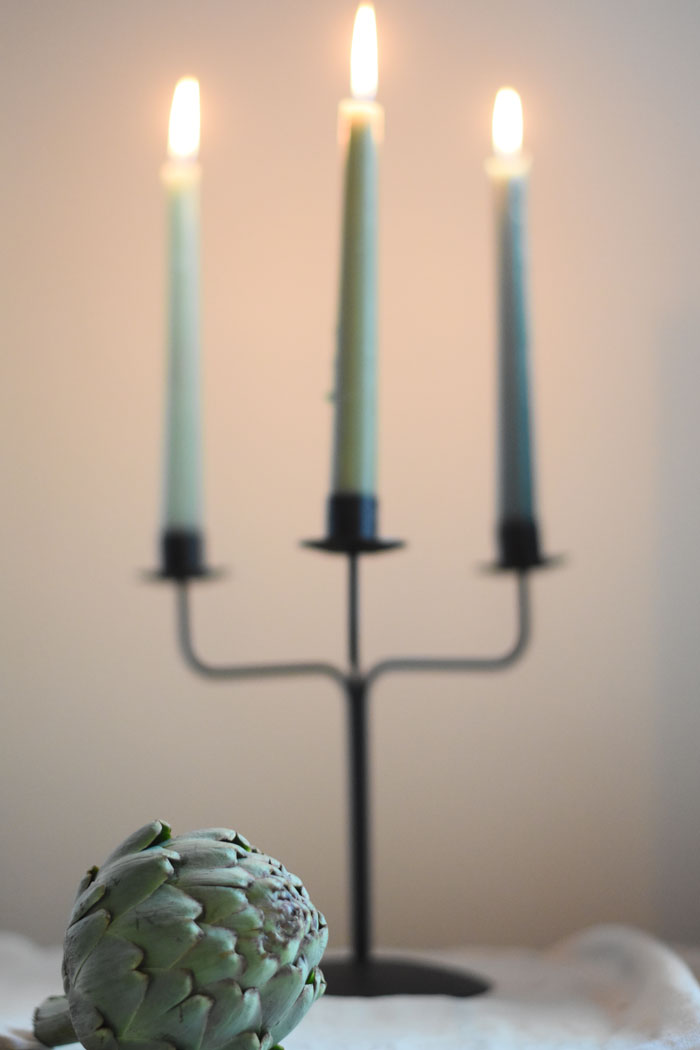 Pale green taper candles in a simple candelabra are on on-trend twist to this classic staple of table decor