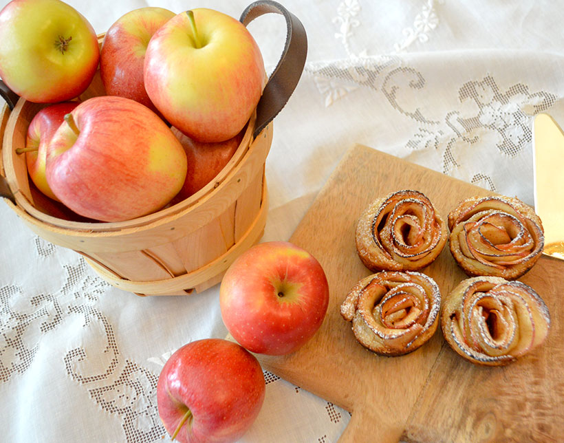 A basket of red apples and apple roses desserts on wood board