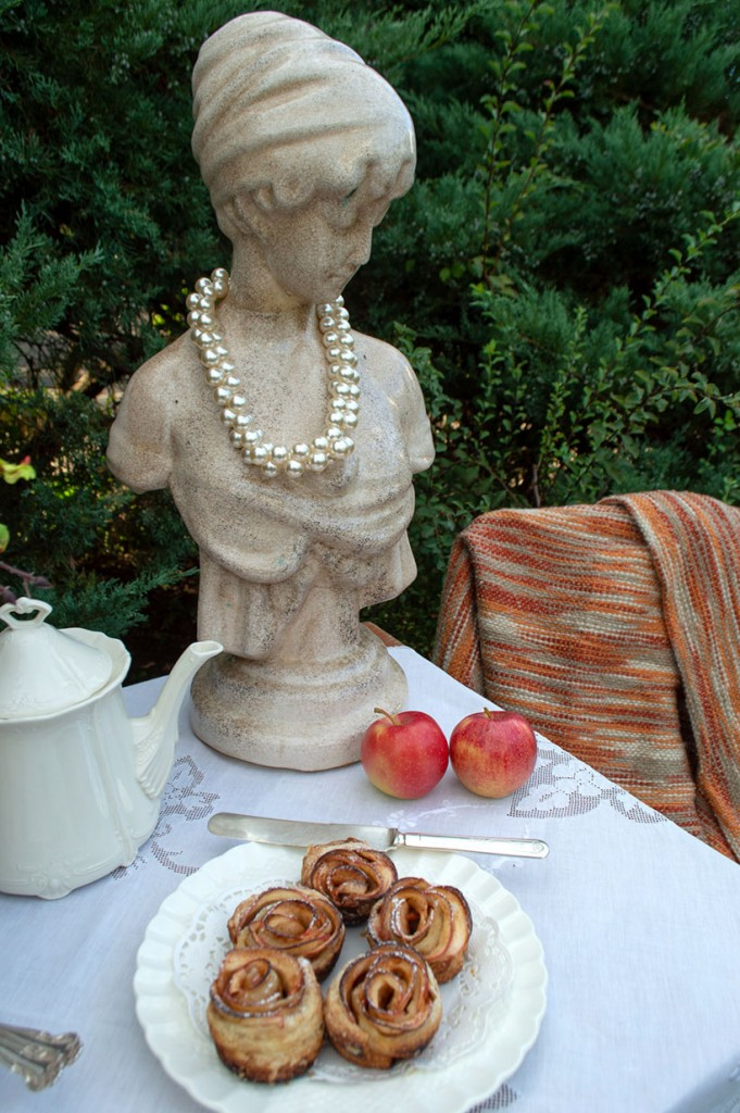 Apple rose desserts next to a tea pot and a statue