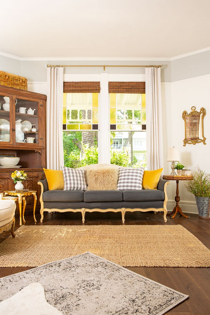 A gray Victorian-style sofa with marigold yellow pillows.