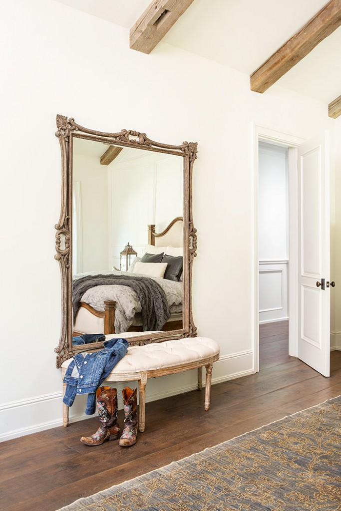 A gilt mirror and tufted bench are elegant accents in this rustic bedroom