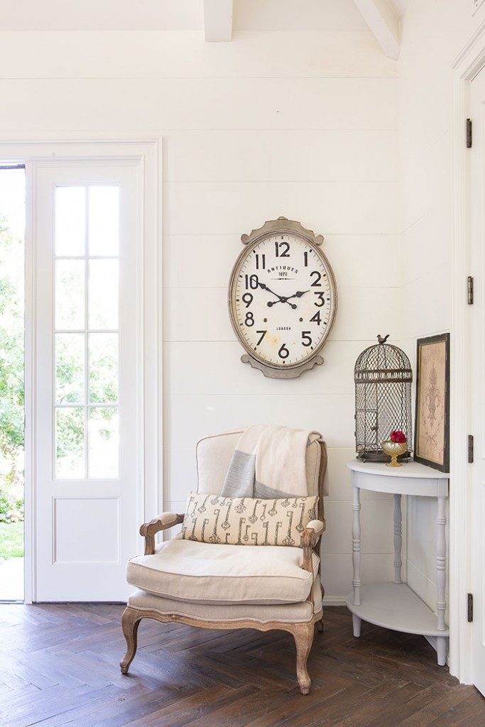 A white bergere chair with a clock overhead and birdcage vignette nearby create an elegant rustic space