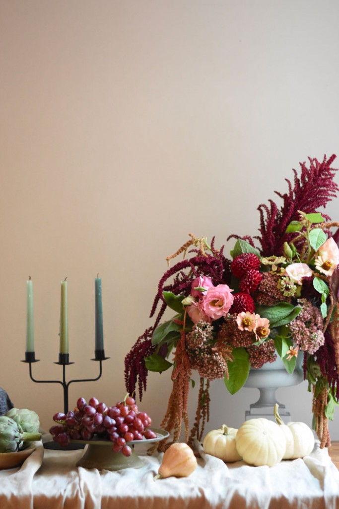 Fall table decor with harvest vegetables, grapes, candles and a fall floral arrangement.