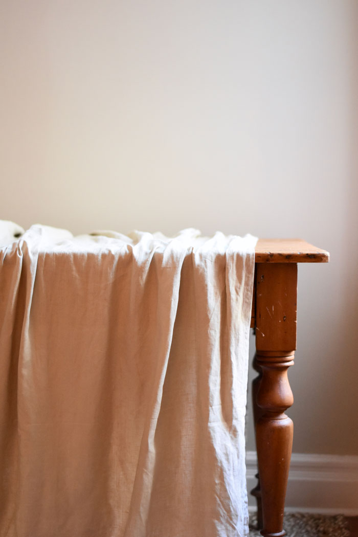 A linen tablecloth on a wood table is the perfect base for fall table decor