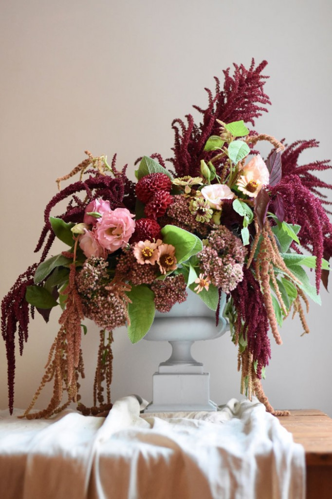 Fall flowers like amaranth, dahlias and zinnias fill a classic urn for a beautiful harvest floral arrangement