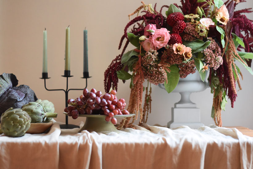 Fall table decor with harvest vegetables, candles and a fall floral arrangement
