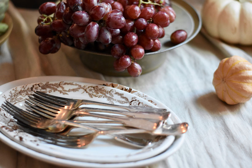 Vintage silverware, antique ironstone transferware and red grapes in a bowl