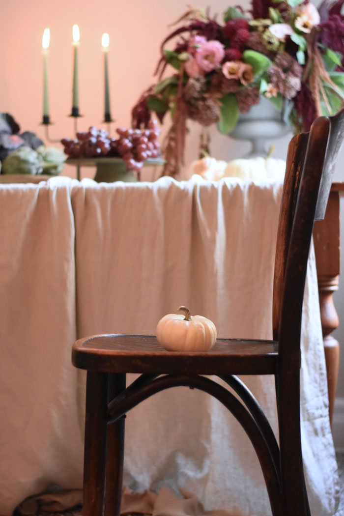 Romantic fall table decor with harvest vegetables, pumpkins and a fall floral arrangment